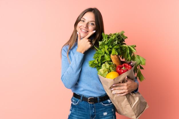 Junge litauische frau, die eine einkaufstasche des lebensmittels glücklich und lächelnd hält