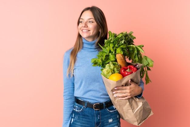 Junge litauische frau, die eine einkaufstasche des lebensmittels hält, die zur seite schaut und lächelt