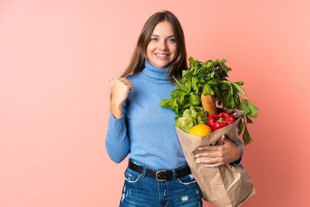 Junge litauische frau, die eine einkaufstasche des lebensmittels hält, die zur seite zeigt, um ein produkt zu präsentieren