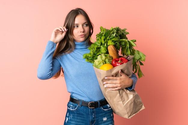Junge litauische frau, die eine einkaufstasche des lebensmittels hält, die zweifel hat und denkt
