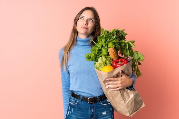 Junge litauische frau, die eine einkaufstasche des lebensmittels hält und nach oben schaut