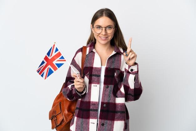 Junge litauische frau, die eine großbritannienflagge lokalisiert auf weißer wand hält, die eine große idee aufzeigt