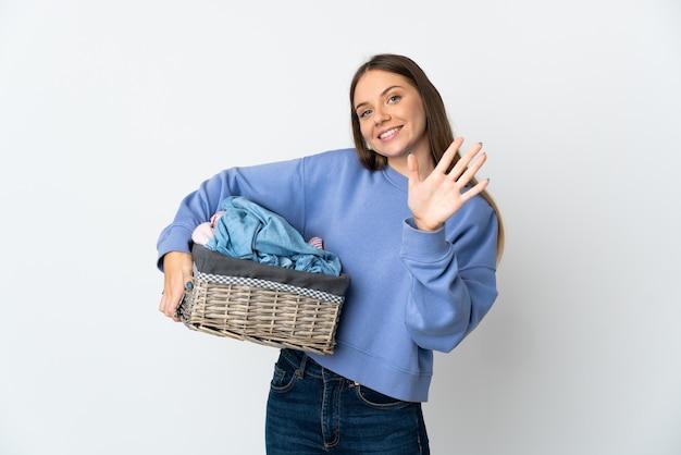 Junge litauische frau, die einen kleiderkorb lokalisiert auf weißem hintergrund hält, der fünf mit den fingern zählt