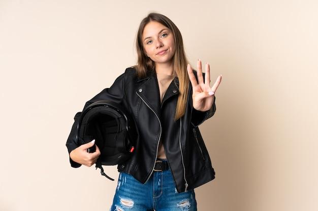 Junge litauische frau, die einen motorradhelm lokalisiert auf beige glücklich hält und vier mit den fingern zählt