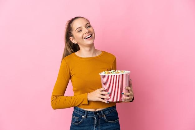 Junge litauische frau isoliert, die einen großen eimer popcorn hält