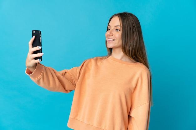 Junge litauische frau lokalisiert auf blauem hintergrund, der ein selfie mit handy macht