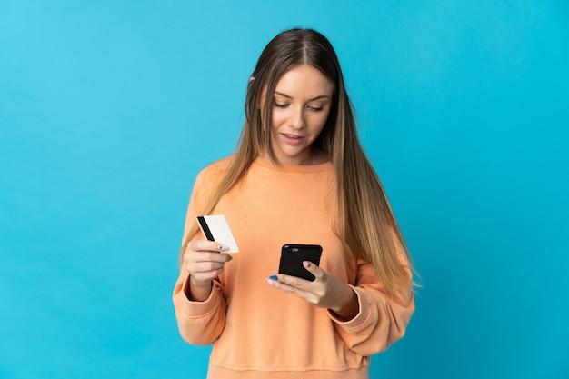 Junge litauische frau lokalisiert auf blauem hintergrund, der mit dem handy mit einer kreditkarte kauft