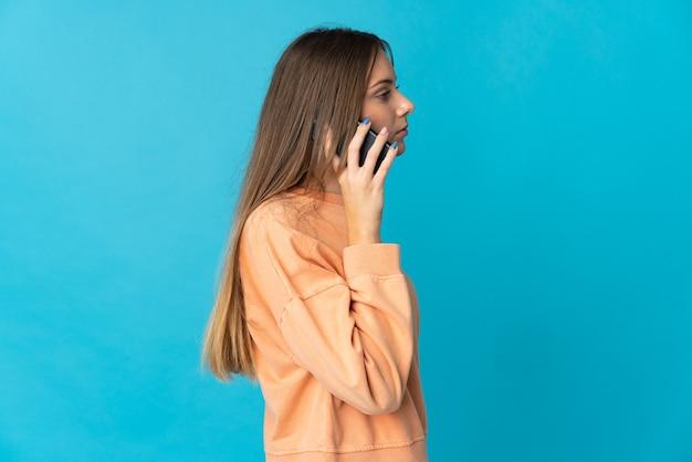 Junge litauische frau lokalisiert auf blauer wand, die ein gespräch mit dem mobiltelefon mit jemandem hält