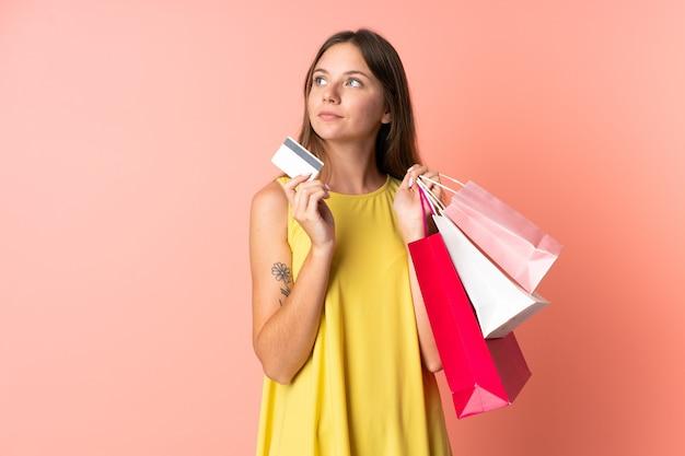 Junge litauische frau lokalisiert auf rosa, die einkaufstaschen und eine kreditkarte hält und denkt