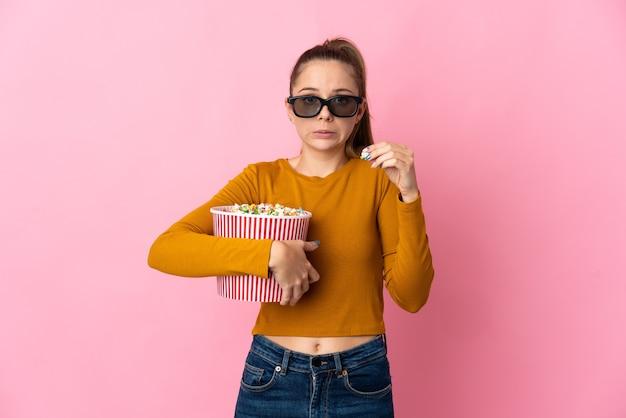 Junge litauische frau lokalisiert auf rosa hintergrund mit 3d-brille und hält einen großen eimer popcorn