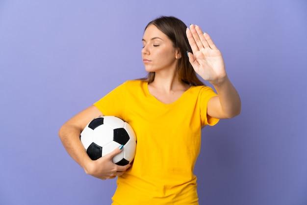 Junge litauische fußballspielerfrau lokalisiert auf lila hintergrund, der stoppgeste macht und enttäuscht