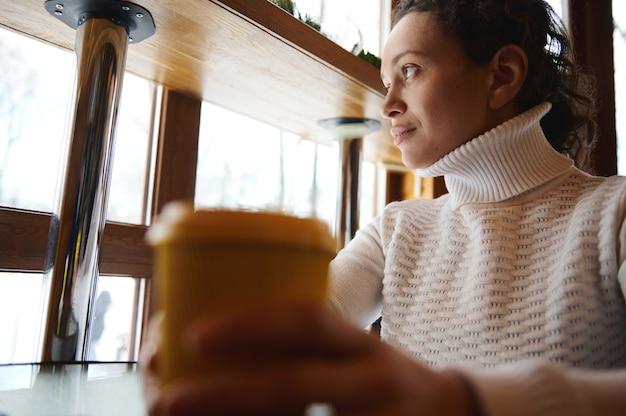 Junge lockige brünette frau mit gelbem pappbecher des leckeren kaffees, der aus dem fenster auf das café schaut