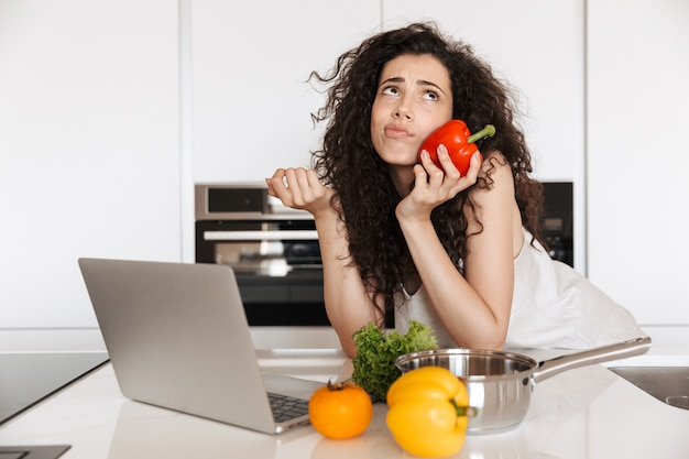 Junge lockige frau 20s hält süßes papier und schaut nach oben, während sie silbernen laptop zum kochen des abendessens im kücheninneren verwendet