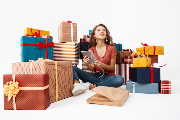 Junge lockige frau, die auf boden unter geschenkboxen mit gerade geöffneter geschenk-tablette sitzt