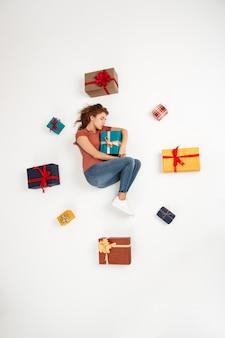 Junge lockige frau, die unter geschenkboxen liegt