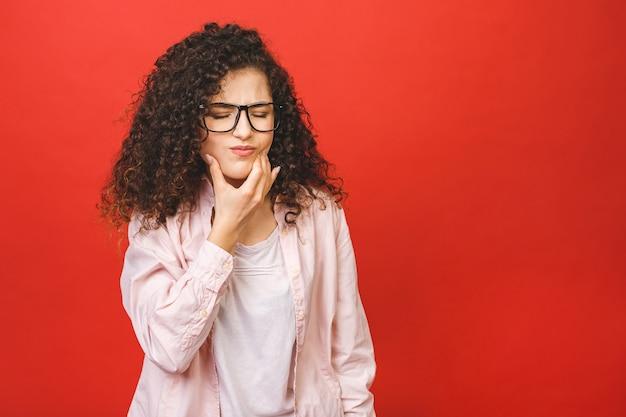 Junge lockige frau über isoliertem rotem hintergrund, der mund mit hand mit schmerzhaftem ausdruck wegen zahnschmerzen oder zahnkrankheit auf zähnen berührt. zahnarztkonzept.