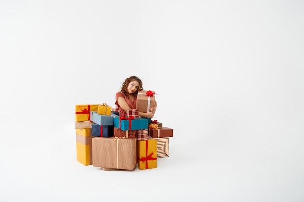 Junge lockige frau unter geschenkboxen