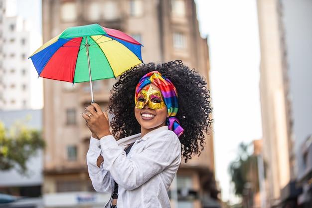Junge lockige haarfrau, die die brasilianische karnevalsparty mit frevo regenschirm auf straße feiert.