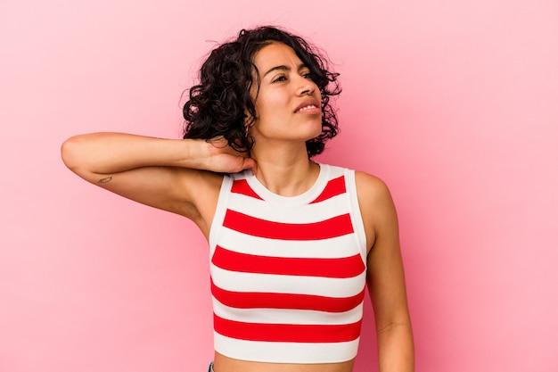 Junge lockige lateinische frau einzeln auf rosafarbenem hintergrund mit nackenschmerzen aufgrund von stress, massieren und berühren mit der hand.
