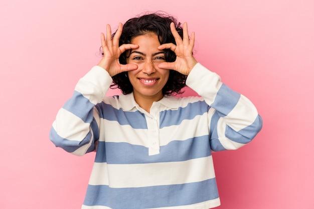 Junge lockige lateinische frau isoliert auf rosa hintergrund, die ein okayzeichen über den augen zeigt