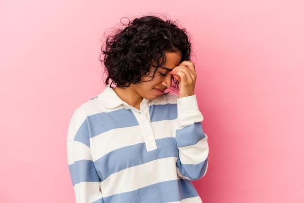 Junge lockige lateinische frau isoliert auf rosa hintergrund mit kopfschmerzen und berührt die vorderseite des gesichts.