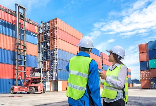 Junge logistische geschäftsleute, die im logistischen hafen arbeiten