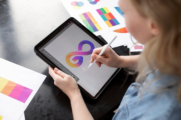 Junge logodesignerin, die an einem grafiktablett arbeitet