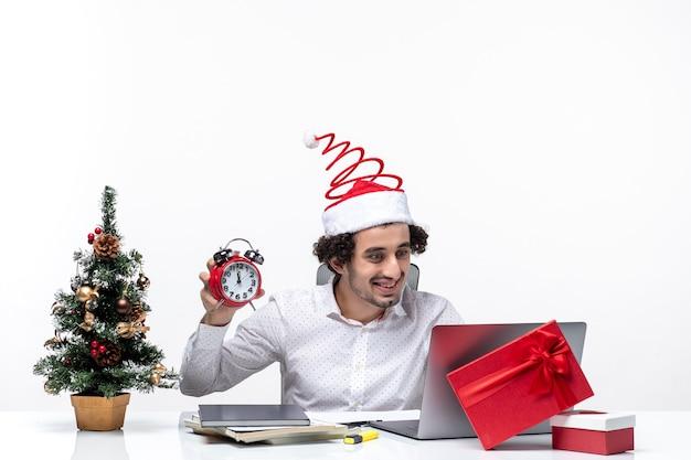 Junge lustige emotionale aufgeregte geschäftsperson mit weihnachtsmannhut und halten und zeigen der uhr, die im büro auf weißem hintergrund stockfoto sitzt
