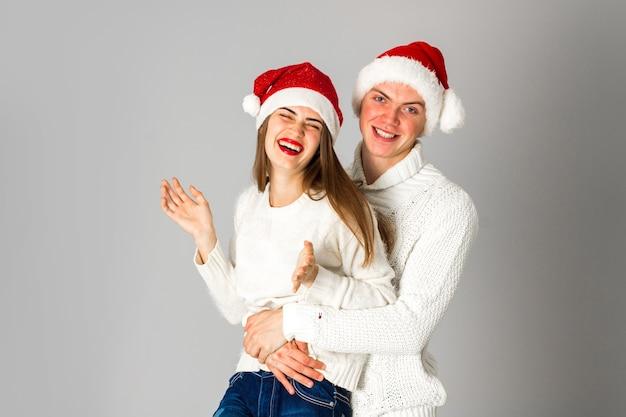 Junge lustige paare feiern weihnachten im studio auf grauem hintergrund