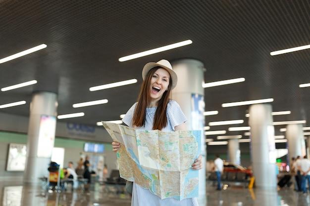 Junge lustige reisende touristenfrau mit hut mit papierkarte, suche nach route beim warten in der lobbyhalle am internationalen flughafen international