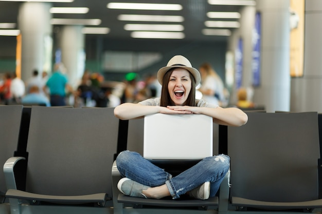 Junge lustige reisende touristin sitzt mit laptop mit gekreuzten beinen, während sie in der lobbyhalle am internationalen flughafen wartet?