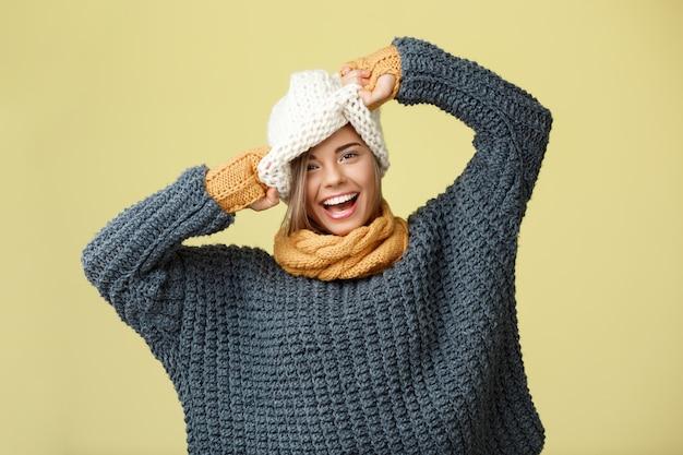 Junge lustige schöne blondhaarige frau im strickmützenpulloverschal und in den fäustlingen, die auf gelb lächeln.