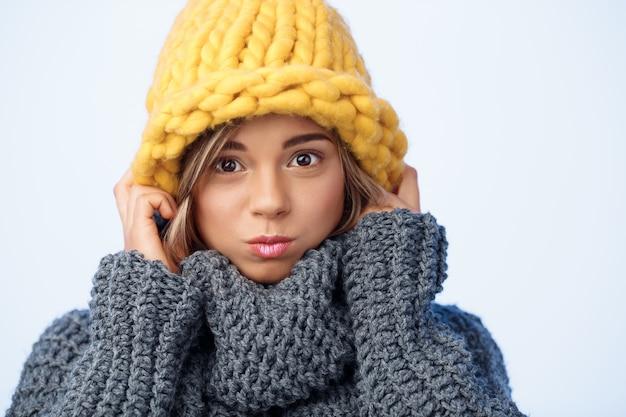 Junge lustige schöne blondhaarige frau in der strickmütze und im pullover, die auf blau lächeln.