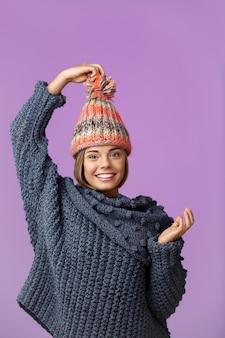 Junge lustige schöne blondhaarige frau in der strickmütze und im pullover lächelnd posiert auf veilchen. speicherplatz kopieren.