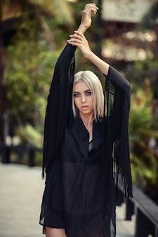 Junge luxusblondine in einem schwarzen hemd lächelt an der kamera. palmen.