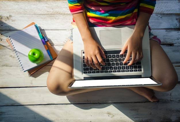 Junge mädchen benutzen einen laptop auf einem bretterboden. und sonnenschein