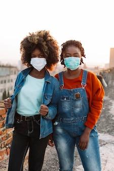 Junge mädchen der vorderansicht, die mit medizinischen masken aufwerfen