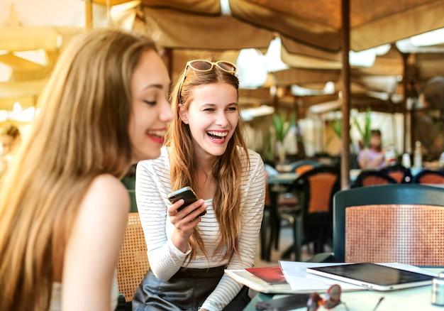 Junge mädchen, die auf der terrasse eines cafés lachen