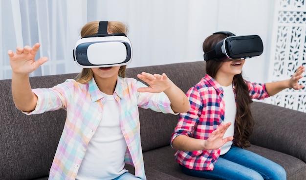 Junge mädchen, die einen kopfhörer der virtuellen realität berühren ihre hände in der luft verwenden