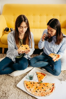Junge mädchen, die pizza teilen und kühlen