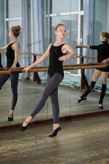Junge mädchen, die während des ballettunterrichts trainieren