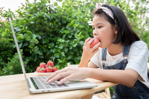 Junge mädchen essen apfel und lernen über online-lektionen per laptop im vorgarten.