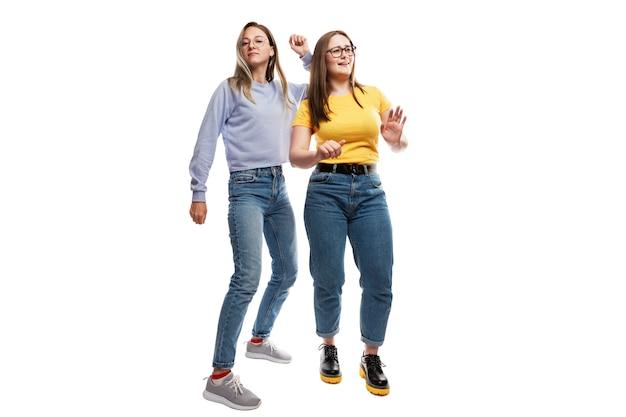 Junge mädchen freundinnen in jeans tanzen emotional. festliche fröhliche stimmung. .