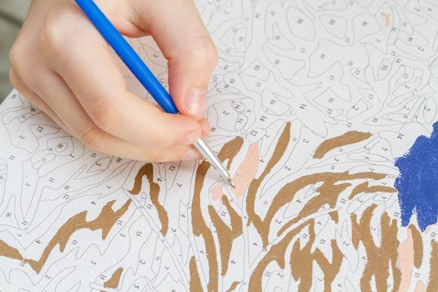 Junge mädchen hand zeichnet mit einem pinsel malen nach zahlen auf leinwand