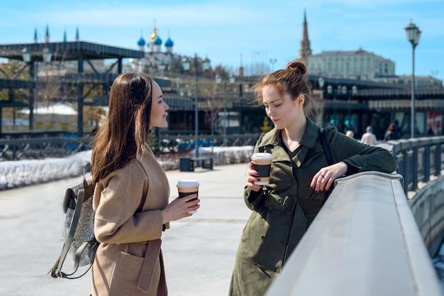 Junge mädchen in mänteln und kaffee sprechen am wasser von kasan. kaffeepause