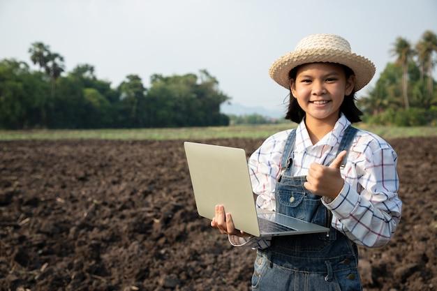 Junge mädchen konsultierten und planten das pflanzen von mais oder grünen bohnen mit einem computergesteuerten laptop auf dem reisfeld. landwirt ist ein beruf, der geduld und fleiß erfordert. bauer sein.