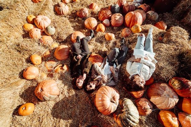 Junge mädchen liegen auf heuhaufen zwischen kürbissen