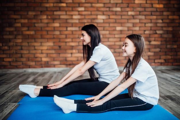 Junge mädchen machen yoga drinnen. mutter und tochter machen gymnastik und dehnen sich im yogazentrum.