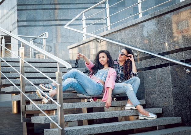 Junge mädchen mit skateboard sitzen auf der treppe