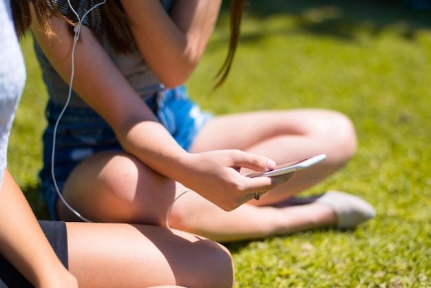 Junge mädchen mit zwei freunden, die musik mit kopfhörern im park hören